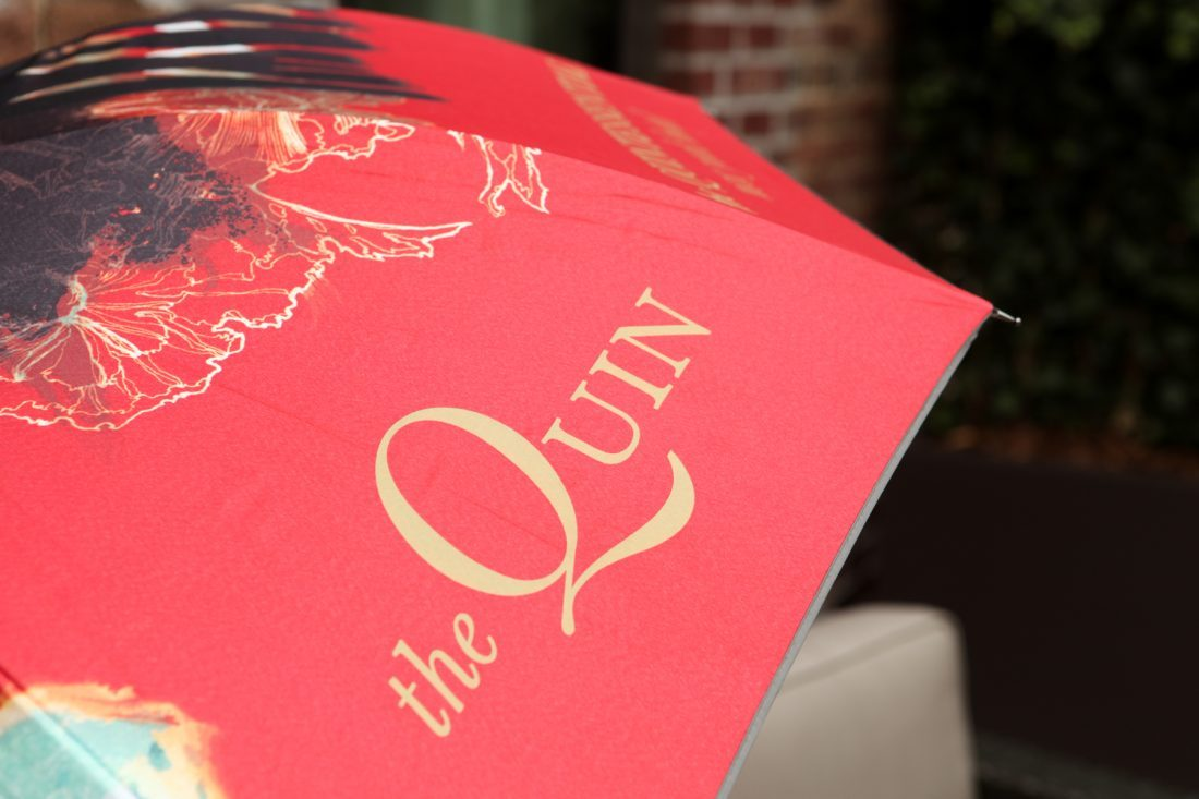 Quin brand name logo on umbrella, red and gold color palette, custom branded boutique hotel guest amenity