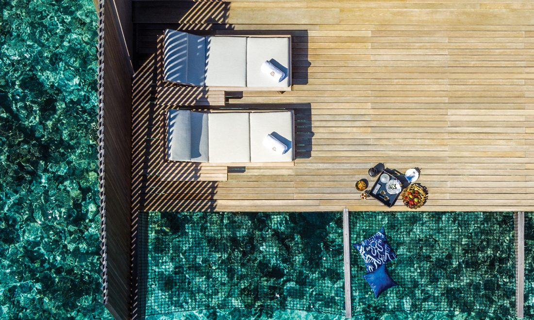 aerial view of lounge chairs on dock over water at luxury hotel resort property, hospitality lifestyle marketing